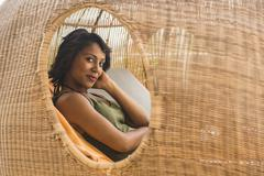 African American woman lounging in cabana Stock Photos