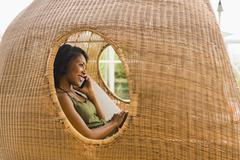 African American woman talking on cell phone in cabana Stock Photos