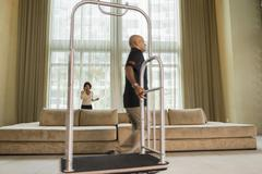 Bellhop pulling cart in hotel lobby Stock Photos
