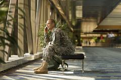 Caucasian soldier talking on cell phone in airport Stock Photos