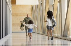 Returning soldier greeting family in airport Stock Photos
