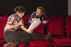 Actors rehearsing in red theater seats Stock Photos