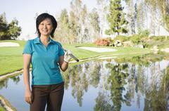 Korean woman smiling on golf course near water hazard Kuvituskuvat