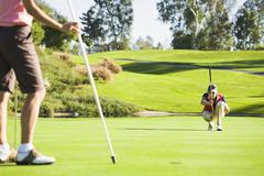 Women planning putt on green at golf course Stock Photos