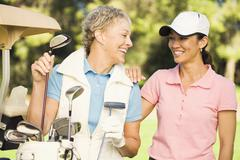 Women laughing on golf course Stock Photos