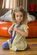 Caucasian preschooler girl playing dress-up with necklace Stock Photos