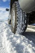 Close up of car tires driving in snow Stock Photos