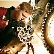 Caucasian mechanic examining motorcycle parts Stock Photos