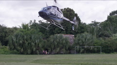 Military helicopter landing on grass field, Guatemala Stock Footage