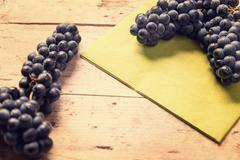 Blue grapes on wooden table, vintage filtered - stock photo