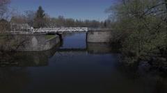 4k aerial cyclist crosses old stone bridge Stock Footage