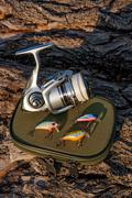 Fishing reel and various kind of plastic baits on the natural background. - stock photo
