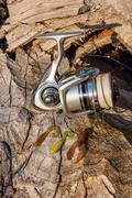 Fishing reel and various kind of silicon baits on the natural background. Stock Photos