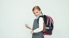Schoolgirl child 7-8 years with backpack using mobile phone on white background Stock Footage