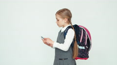 Portrait schoolgirl 7-8 years with backpack using mobile phone on white Stock Footage