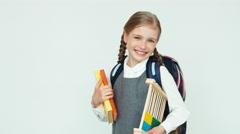 Portrait cute schoolgirl child 7-8 years with backpack holding abacus and book Stock Footage