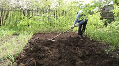 The woman leveled the soil with a rake Stock Footage