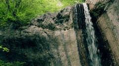 Small waterfall in mountains. Water rushes from stone visor into small lake. - stock footage
