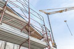 Building armor for house under restoration and crane. Stock Photos