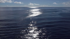 sun reflecting and glinting off waves ripples across water, horizon - stock footage