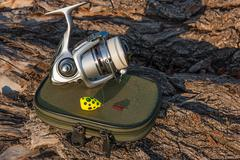 Fishing reel and fishing bait on the natural background. Stock Photos