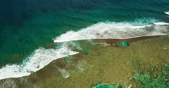 Aerial view flying over coral reef and breaking ocean waves Stock Footage