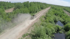 Flying over the military vehicle driving in rough wooded country Stock Footage