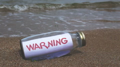 Warning written on a message washed ashore Stock Footage