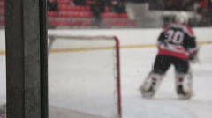 Goaltender with ice hockey stick warming up before match, skating near the net Stock Footage