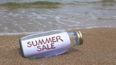 Summer sale concept written on a message washed ashore Stock Footage