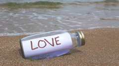 Lost love concept written on a message washed ashore Stock Footage