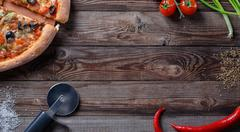 Tasty pizza with ingridients on a wooden board Stock Photos