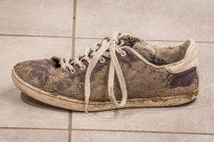 Dirty shoe with white laces - stock photo