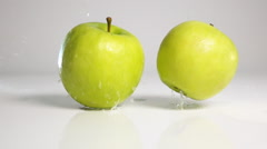 Two apples drop down on white surface Stock Footage
