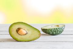 Avocado in half on a table Stock Photos