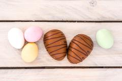Easter candy eggs on a wooden table - stock photo