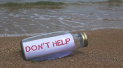 Do not help request  written on a message washed ashore - stock footage