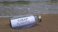 Chep flights written on a message washed ashore Stock Footage