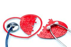 Heart disease, Split heart-shaped puzzle with stethoscope - stock illustration
