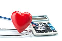 Red heart and calculator with stethoscope on white background Stock Illustration