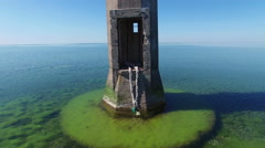 4K. Flight and takeoff over old lighthouse standing in the sea, aerial view. - stock footage