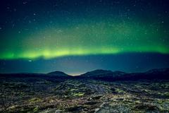 Aurora Borealis over distant mountains - stock photo