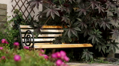 View of the exterior of a home. Wrought iron bench with wooden seats. - stock footage
