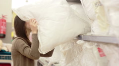 Young woman chose a pillow in a supermarket Stock Footage