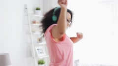 happy african woman in headphones dancing at home - stock footage