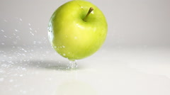 Green apple fall on white surface Stock Footage