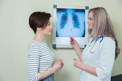 doctor explaining diagnosis to her female patient analysing x-ray photography - stock photo