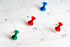 green red blue pins on calendar grid - stock photo