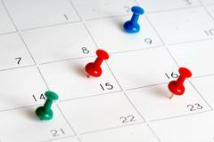 Green red blue pins on calendar grid Stock Photos