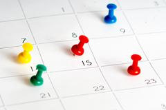 multiple color pins on calendar grid - stock photo